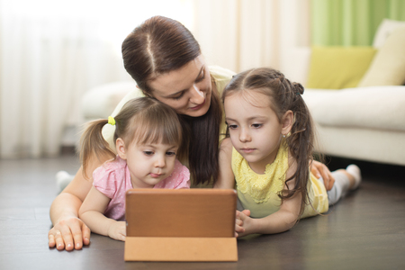 Mother with kids use ipad lying on floor in living room