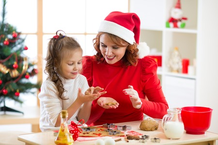 Mother and daughter baking Christmas cookies at decorated tree. Mom and child bake Xmas sweets. Family with kids celebrating Christmas at home.