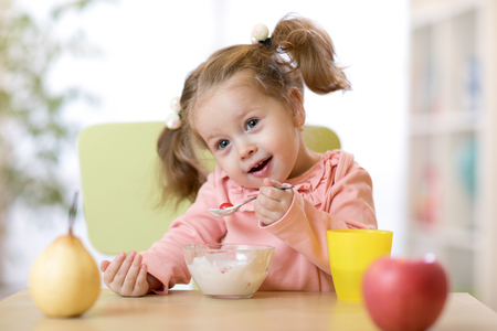Portrait of cute little girl eating fruits and yogurt for breakfast at home