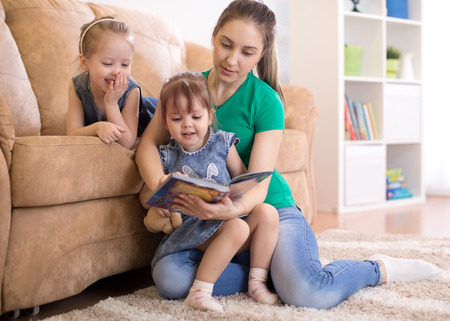 Mother and cheerful daughters reading book in living room