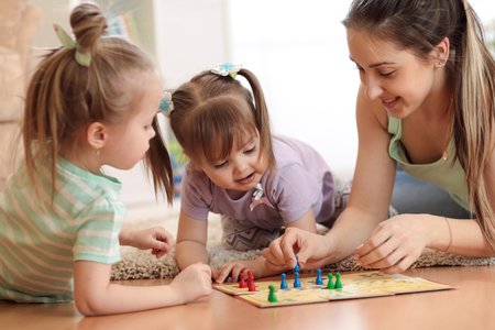 Happy family. Young mother playing ludo boardgame with her daughters while spending time together at home.