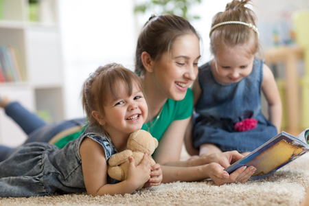 Young woman with children read storybook