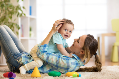 Happy mother and child son lying on the floor and playing indoor
