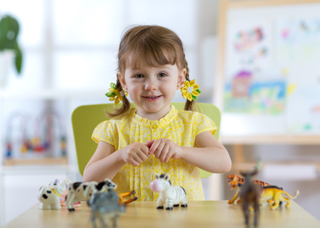 child playing with animal toys at table in kindergarten or home