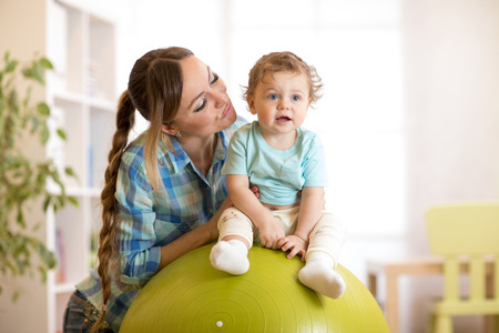 kid boy and mother do gymnastics with fitness ball