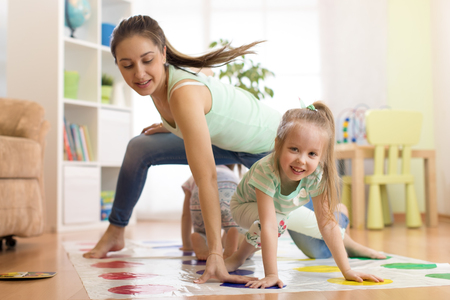 Young mother playing twister with her kids. Cheerful family at home. Happy family playing together