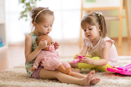 kinderen spelen dokter met pop binnen Stockfoto