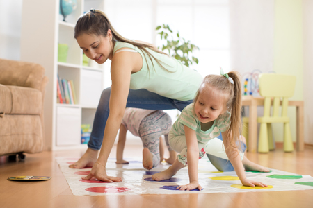 Mother playing twister with her children daughters. Happy family have a fun time in holiday Stock Photo
