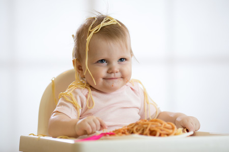 Little baby eating her lunch and making a mess Stock Photo