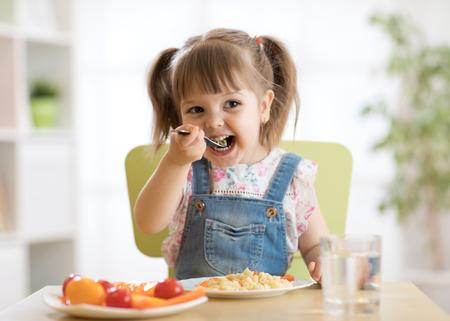 kid girl eating healthy food at home Stock Photo