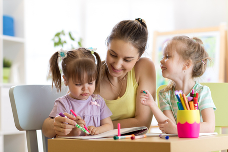 Mother and kids daughters are learning to write. Adult woman teaches children writing.
