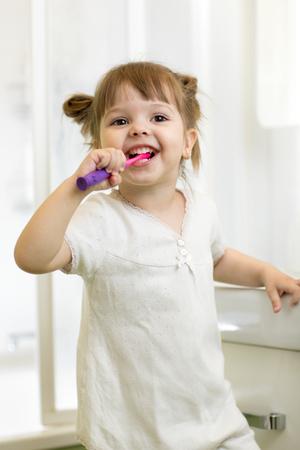 Dental hygiene. Smiling child girl brushing her teeth