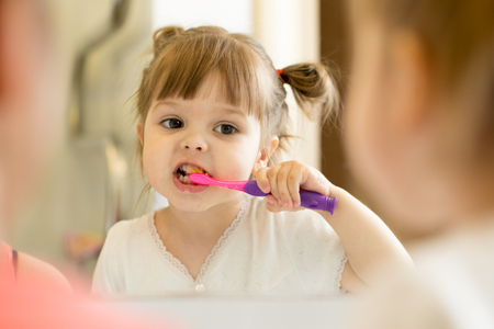 Cute kid girl looking at mirror using toothbrush cleaning teeth in bathroom every morning and night.