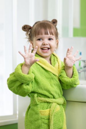 Happy child washing hands and showing soapy palms