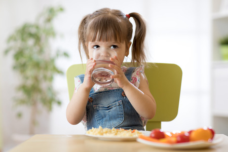 Child girl eating and drinking in kindergarten