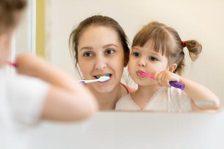 mother teaching child daughter teeth brushing