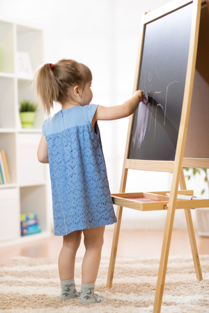 Child painting on board in school. Stock Photo