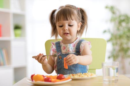 Child little girl eating healthy vegetables