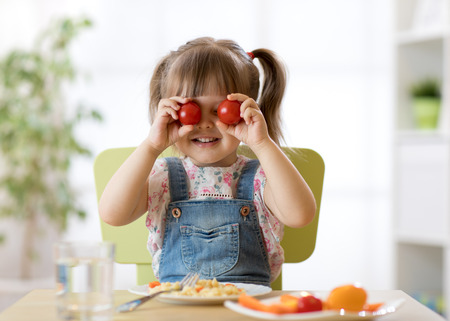 Happy kid having fun with food vegetables at kitchen holds tomatoes before his eyes like in glasses