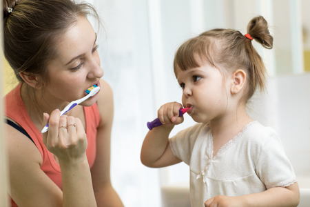 Mother and child brushing teeth together in the morning - dental care concept Stock Photo