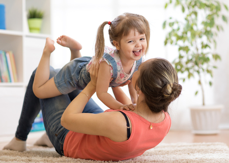 Mother and daughter having a fun on floor at home. Woman and child relaxing together.