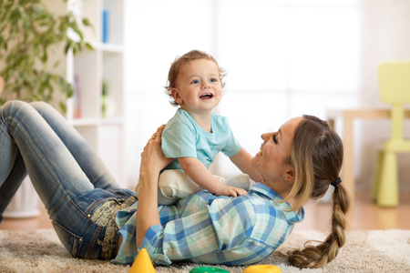 Mother and baby son having a fun on floor at home. Woman and child relaxing together. Stock Photo