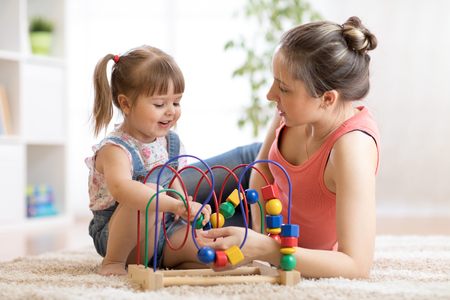 Child toddler girl and mom play with educational toy in nursery at home.