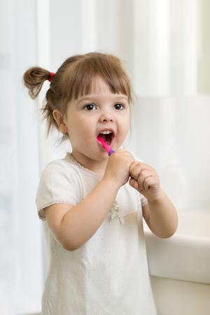 A cute little girl brushing her teeth in bathroom