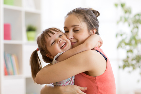 Mom and daughter embracing at home