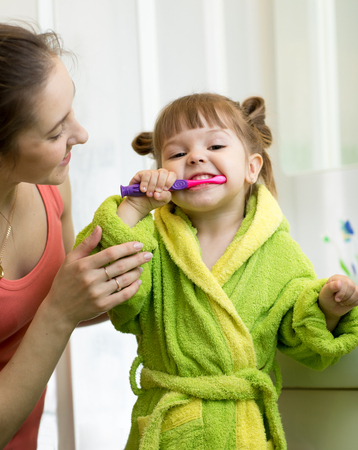 Mother teaches her little daughter how to brush teeth Stock Photo