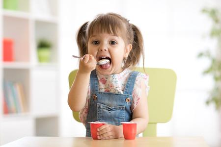 A cute little girl eating yogurt.