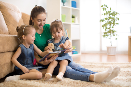 Happy mother and little daughters reading a book together in the living room at home. Family activity concept. Stock Photo