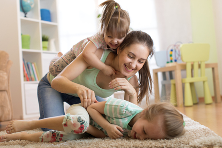 Closeup of happy family. Joyful mom and her kids having a fun pastime on floor in living room. Stock Photo