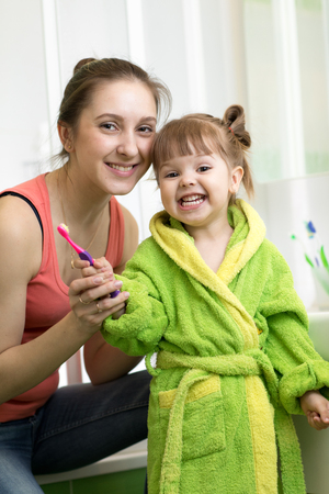 Mother with her little daughter brushing teeth