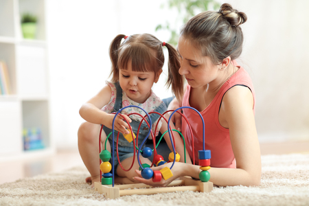 Child girl with mom plays with educational toy in nursery at home.