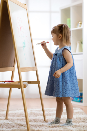 Kid girl drawing on white board Stock Photo