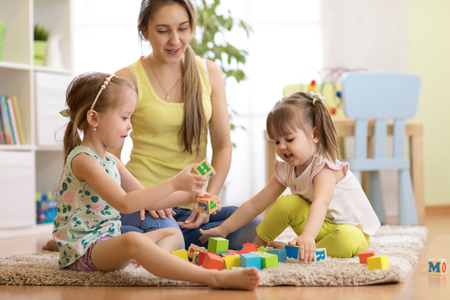 Family mom and daughters playing with block toys in living room