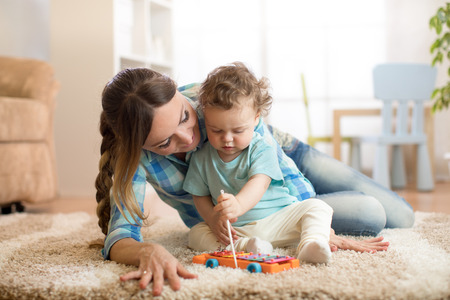 cute little toddler boy and babysitter playing with toy by the home