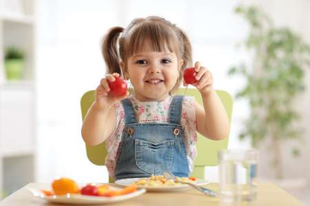 Healthy kids nutrition concept. Cute toddler girl sitting at table with plate of salad, vegetables, pasta in room. Child eating healthy food. Stock Photo