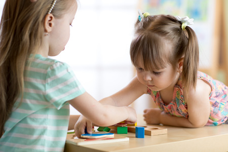 Kids playing with colorful toys. Two children girls at home or daycare centre. Educational child toys for preschool and kindergarten.