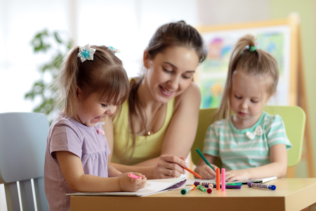 Children students with teacher drawing in art school class. Mother and kids at home. Children indulge. Stock Photo