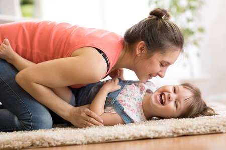 Family - mom and daughter having a fun on floor at home. Woman and child relaxing together. Stock Photo