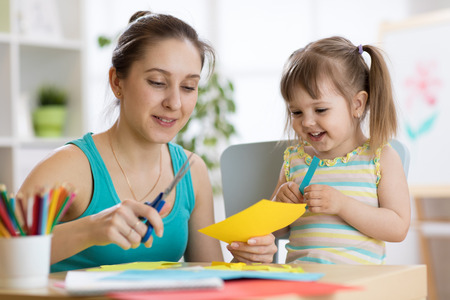 Mom helping her child to cut colored paper Stock Photo