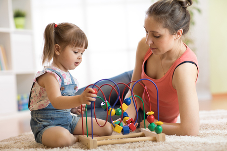 Kid girl plays with educational toy indoor. Happy mother teaching her smart daughter