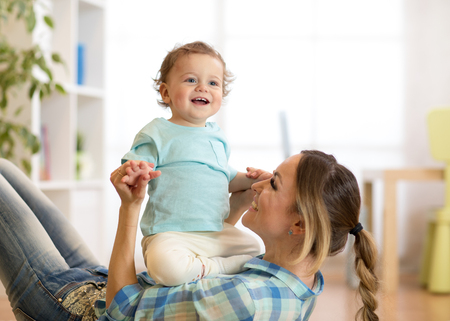 Smiling kid and mom having a fun pastime on floor in children room at home