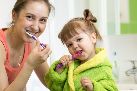 Mom and little kid daughter brushing teeth in bathroom Stock Photo