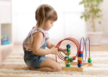 kid girl plays with educational toy indoors Stock Photo