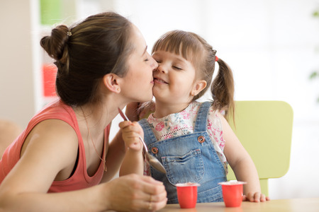 Cute child girl is having healthy breakfast. Her mother is kissing her with love. Child is sitting at table and eats yoghurt Stock Photo