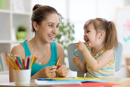 Mom helping her child to work colored paper
