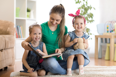 pretty young mother reading a book to her daughters Stock Photo